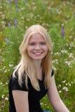 Gelukkig die blondemeisje door bloemen wordt omringd Royalty-vrije Stock Foto's