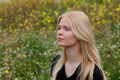 Gelukkig die blondemeisje door bloemen wordt omringd Stock Afbeeldingen