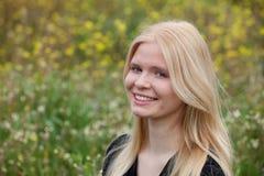 Gelukkig die blondemeisje door bloemen wordt omringd Royalty-vrije Stock Afbeeldingen