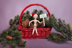 Gelukkig die December-teken door houten verbonden mannequinpop wordt gehouden die een rode Santa Claus-hoed dragen stock foto