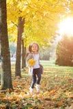 Gelukkig die meisje in de herfstpark in werking wordt gesteld stock fotografie