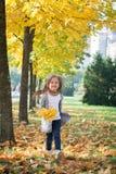 Gelukkig die meisje in de herfstpark in werking wordt gesteld stock foto's