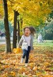 Gelukkig die meisje in de herfstpark in werking wordt gesteld royalty-vrije stock foto