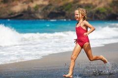 Gelukkig die meisje langs overzeese branding door zandstrand in werking wordt gesteld royalty-vrije stock foto's