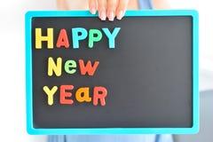 , Gelukkig die Nieuwjaar ` op het bord met magnetische gekleurde brievenblokken wordt geschreven Royalty-vrije Stock Foto's