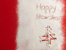 Gelukkig die Nieuwjaar op witte sneeuw wordt geschreven Stock Afbeelding