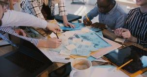 Gelukkig divers multi-etnisch beambten creatief team die achter lijsthoogtepunt samenwerken van nota's, brainstormingszitting stock video