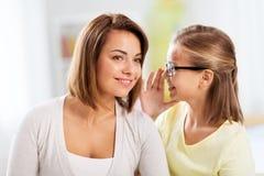 Gelukkig dochter het fluisteren geheim aan haar moeder stock afbeeldingen