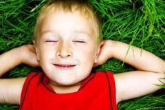Gelukkig dromend kind op vers gras Royalty-vrije Stock Afbeeldingen