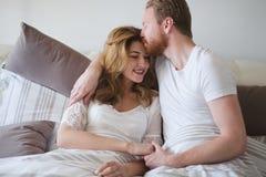 Gelukkig echtpaar die romantisch en sensueel in bed zijn stock foto
