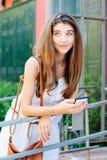 Gelukkig en dromerig meisje die haar mobiele telefoon met behulp van Royalty-vrije Stock Foto