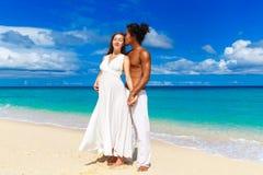Gelukkig en jong zwanger paar die pret op een tropisch strand hebben Royalty-vrije Stock Foto's