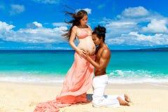 Gelukkig en jong zwanger paar die pret op een tropisch strand hebben Royalty-vrije Stock Afbeelding