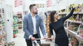 Gelukkig en mooi paar die en bij kruidenierswinkelopslag lachen winkelen stock videobeelden