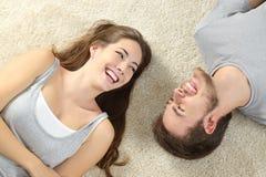 Gelukkig en paar die liggen lachen Stock Fotografie