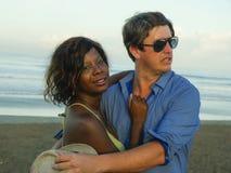 Gelukkig en romantisch gemengd raspaar met aantrekkelijke zwarte afro Amerikaanse vrouw en het witte man spelen op strand die pre stock foto