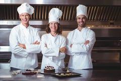 Gelukkig en trotse chef-koks om de cake voor te stellen die zij enkel hebben gemaakt Stock Foto's
