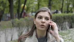 Gelukkig en verrast mooi donkerbruin meisje die op de telefoon op stadsstraat spreken stock footage
