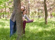 Gelukkig familie en kind in de zomerpark Mensen die en achter een boom verbergen spelen Mooi landschap met bomen en groen gras Stock Afbeeldingen
