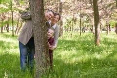 Gelukkig familie en kind in de zomerpark Mensen die en achter een boom verbergen spelen Mooi landschap met bomen en groen gras Royalty-vrije Stock Afbeeldingen