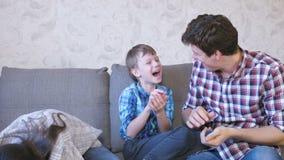 Gelukkig familie mamma, zoon en papa en het spelen met slimes die op de bank zitten Het kijken door het slijm stock video