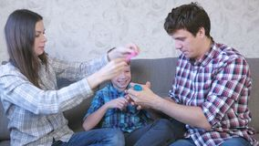 Gelukkig familie mamma, zoon en papa en het spelen met slimes die op de bank zitten Het uitrekken van het slijm stock videobeelden