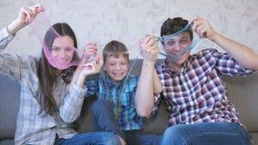 Gelukkig familie mamma, zoon en papa en het spelen met slimes die op de bank zitten Het uitrekken van het slijm Het kijken door stock video