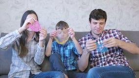Gelukkig familie mamma, zoon en papa en het spelen met slimes die op de bank zitten Het uitrekken van het slijm Het kijken door stock footage