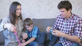 Gelukkig familie mamma, zoon en papa en het spelen met slimes die op de bank zitten Het uitrekken van het slijm stock footage