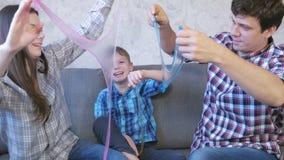 Gelukkig familie mamma, zoon en papa en het spelen met slimes die op de bank zitten Het uitrekken van het slijm Het kijken door stock videobeelden