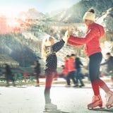Gelukkig familie openluchtijs die bij piste schaatsen De activiteiten van de winter stock foto's