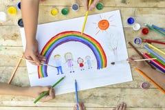 Gelukkig familieconcept Co-verwezenlijking De kinderenhanden trekken op een blad van document: de vader, de moeder, de jongen en  stock foto's