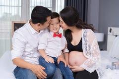Gelukkig familieconcept, zwangere moeder en jongen van het vader de kussende jonge geitje stock foto's