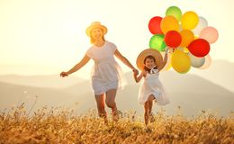 Gelukkig familiemoeder en kind met ballons bij zonsondergang in de zomer royalty-vrije stock afbeeldingen