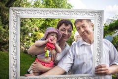 Gelukkig familieportret van vrolijke grootvader met zijn dochter en kleinkind tijdens in openlucht partij stock afbeeldingen