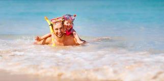 Gelukkig familievader en kind die masker dragen en op beac lachen Stock Foto's