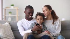 Gelukkig gemengd de papazoon en mamma die van de het behoren tot een bepaald rasfamilie telefoon met behulp van stock video
