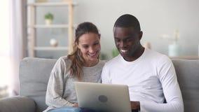 Gelukkig gemengd het behoren tot een bepaald ras jong paar die laptop zitting op bank gebruiken stock videobeelden