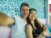 Gelukkig gemengd het behoren tot een bepaald raspaar in liefde glimlachen vrolijk met de knappe Kaukasische mens en mooie Aziatis stock foto's