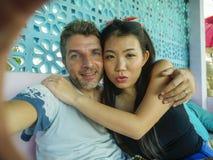 Gelukkig gemengd het behoren tot een bepaald raspaar in liefde glimlachen vrolijk met de knappe Kaukasische mens en mooie Aziatis stock foto