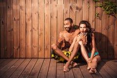 Gelukkig gemengd raspaar die duimen over houten achtergrond tonen Stock Foto's