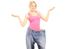 Gelukkig gewichtloos wijfje met oud paar jeans die met hij gesturing Stock Foto's