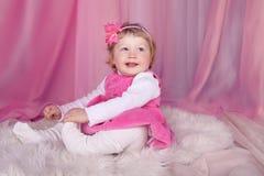 Gelukkig glimlachend grappig meisje dat op bed over roze handelaar in stoffen rust Royalty-vrije Stock Foto's