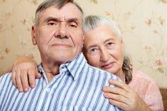 Gelukkig glimlachend hoger paar die samen thuis omhelzen stock afbeeldingen
