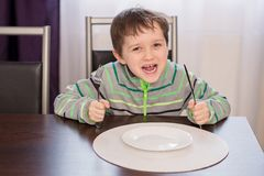 Gelukkig glimlachend jongenskind die op diner wachten stock afbeeldingen
