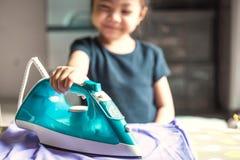 Gelukkig glimlachend Leuk meisje die een overhemd thuis strijken Selecti royalty-vrije stock foto's