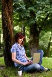 Gelukkig glimlachend meisje die online werken Stock Fotografie
