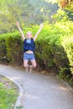 Gelukkig glimlachend meisje die op het park in de dagtijd springen stock afbeeldingen