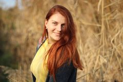 Gelukkig glimlachend meisje met lang rood haar in de herfst parkland stock afbeelding