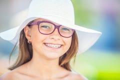 Gelukkig glimlachend meisje met tandsteunen en glazen Orthodontist en tandartsconcept stock fotografie